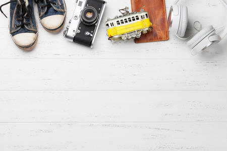 Travel vacation background concept with camera, passport, headphones and tram toy on wooden backdrop. Top view with copy space. Flat lay Stock Photo