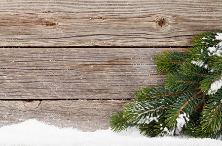 Christmas backdrop with fir tree branch covered by snow in front of wooden wall. Xmas background with space for your greetings