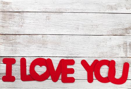 Valentinstaggrußkarte mit ich liebe dich Wörter über hölzernem Hintergrund. Mit Platz für deine Grüße