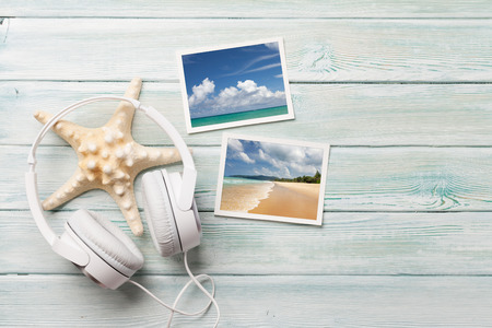 Travel vacation and music concept with headphones, starfish and photos on wooden backdrop. Top view with copy space.