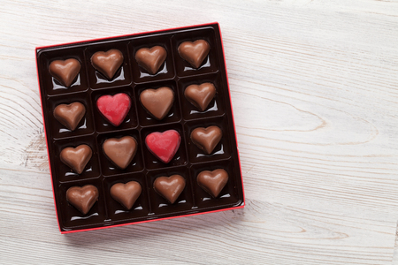 Valentines day with heart chocolate in box on wooden table. Top view with space for your greetings Archivio Fotografico