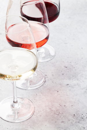 Red, rose and white wine glasses on stone backdrop. With space for your text