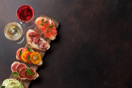 Brushetta oder traditionelle spanische Tapas. Vorspeisen italienische Antipasti-Snacks auf Holzbrett mit Rose und Weißwein. Draufsicht und flach liegen mit Platz für Ihren Text Standard-Bild