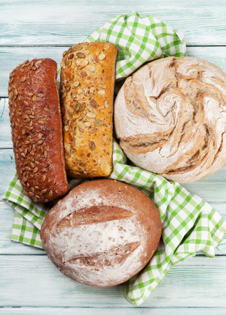 Various crusty bread and buns on white wooden table. Top view Stockfoto - 113023670