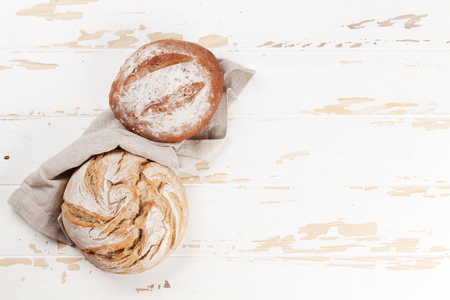 Homemade crusty bread on white wooden table. Top view with space for your text Stockfoto