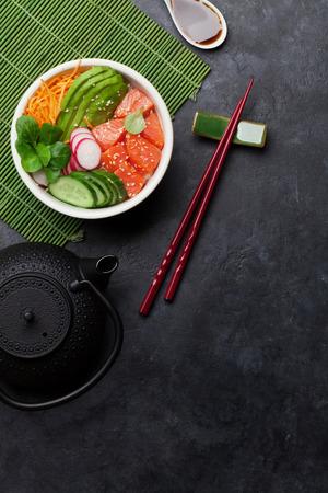 Poke bowl with salmon and vegetables. Traditional Hawaiian raw fish salad. Top view with copy space Zdjęcie Seryjne