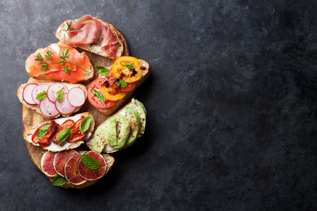 Brushetta or traditional spanish tapas. Appetizers italian antipasti snacks set on wooden board. Top view and flat lay with copy space