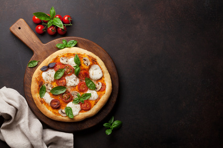 Italian pizza with tomatoes, mozzarella and basil. Top view with space for your text Imagens