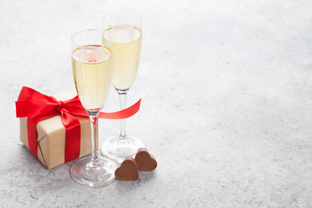 Valentines day greeting card with champagne, gift box and chocolate hearts on stone background. With space for your greetings