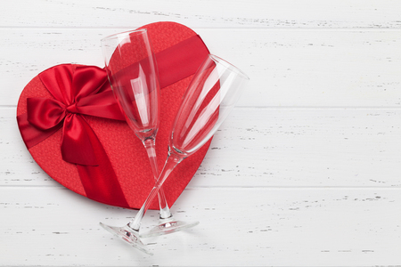 Valentines day greeting card with champagne glasses and heart shaped gift box on wooden background. Top view with space for your greetings. Flat lay Stock Photo