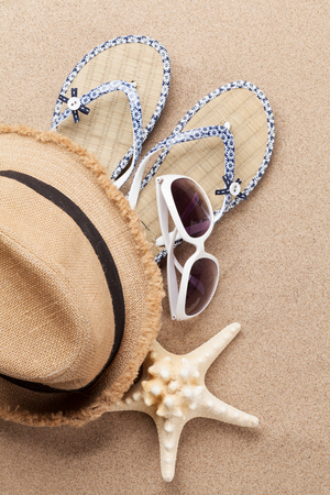 Travel vacation concept with sunglasses and beach hat on sand backdrop. Top view