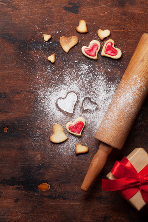 Valentines day greeting card with cooking heart shaped cookies on wooden background. Top view with space for your greetings. Flat lay