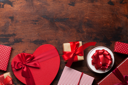 Valentines day greeting card with heart gift boxes on wooden background. Top view with space for your greetings. Flat lay 写真素材