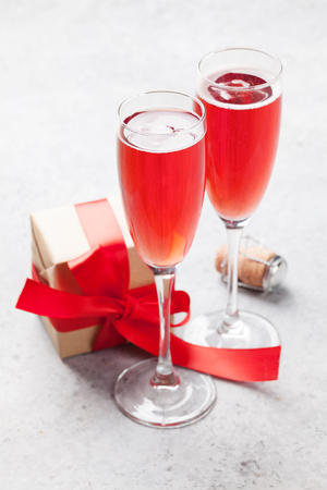 Valentine's day greeting card with champagne and love gift box on stone background