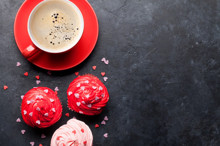 Valentines day greeting card with delicious sweet cupcakes and coffee cup on stone background. Top view with space for your greetings