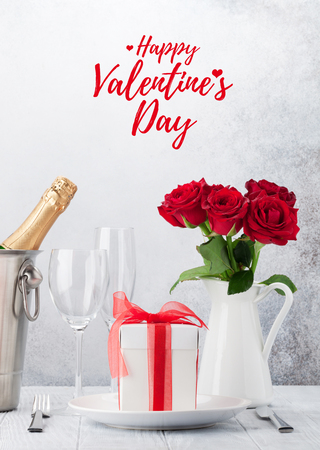 Valentines day greeting card with red rose flowers bouquet, dinner setting and gift box in front of stone wall Stock Photo