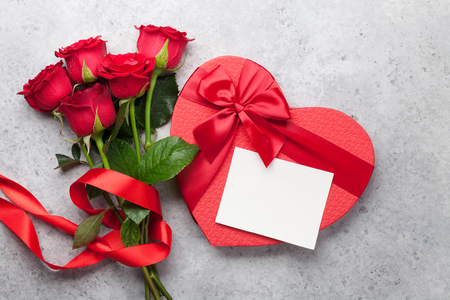 Valentine's day greeting card with red rose flowers bouquet and gift box on stone background. Top view with space for your greetings