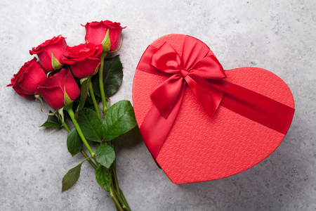 Valentines day greeting card with red rose flowers bouquet and heart gift box on stone background. Top view