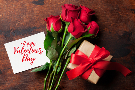 Valentines day greeting card with red rose flowers bouquet and gift box on wooden background. Top view Stock Photo