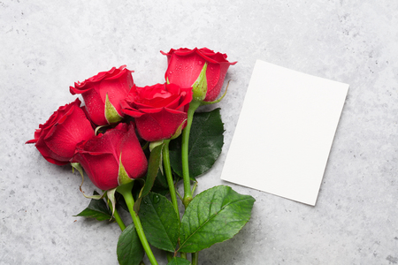 Valentines day greeting card with red rose flowers bouquet on stone background. Top view with space for your greetings