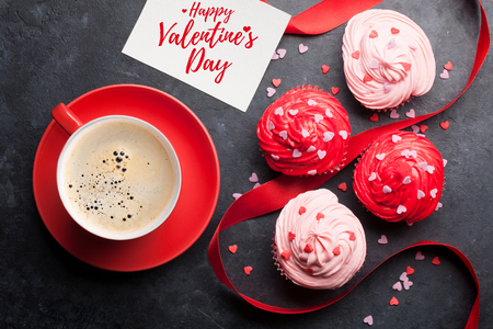 Valentines day greeting card with delicious sweet cupcakes and coffee cup on stone background. Top view Stock Photo