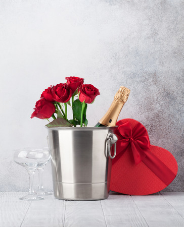 Valentine's day greeting card with red rose flowers bouquet, gift box and champagne in front of stone wall. With space for your greetings Stock Photo