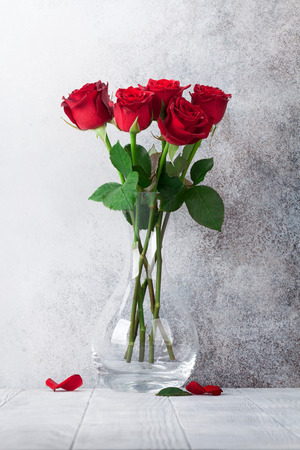 Red rose flowers bouquet in front of stone wall Stock Photo