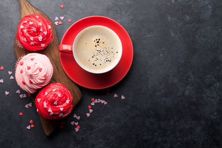 Valentine's day greeting card with delicious sweet cupcakes and coffee cup on stone background. Top view with space for your greetings