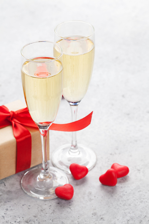 Valentines day greeting card with champagne, gift box and candy hearts on stone background. With space for your greetings Standard-Bild - 115227028