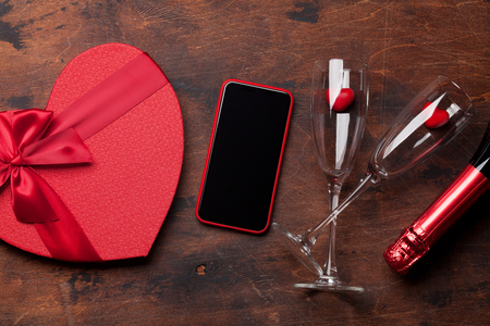 Valentines day greeting card with champagne, gift box and smartphone on wooden background. Top view with space for your greetings or smart phone app. Flat lay