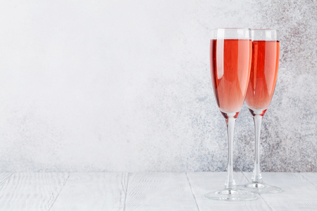 Rose champagne glasses in front of stone wall. With space for your text