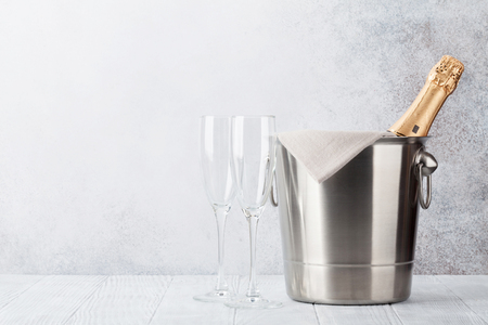 Champagne bottle in bucket and glasses in front of stone wall. With space for your text