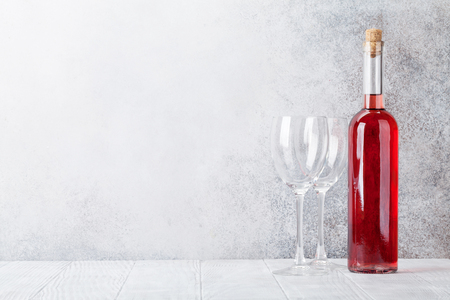 Rose wine bottle and glasses in front of stone wall. With space for your text