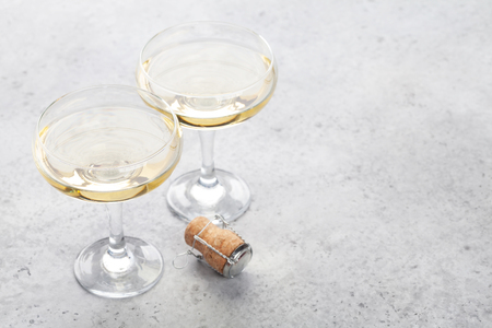Two champagne glasses on stone table. With copy space