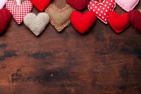 Valentines day greeting card with handmaded heart toys on wooden background. Top view with space for your greetings. Flat lay