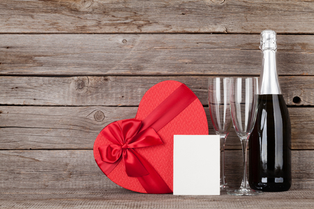 Valentines day greeting card with heart shaped gift box and champagne in front of wooden wall. With space for your greetings