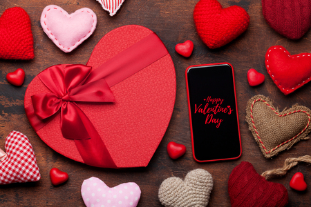 Valentine's day greeting card with knitted hearts, gift box and smartphone on wooden background. Top view with space for your greetings or smart phone app. Flat lay