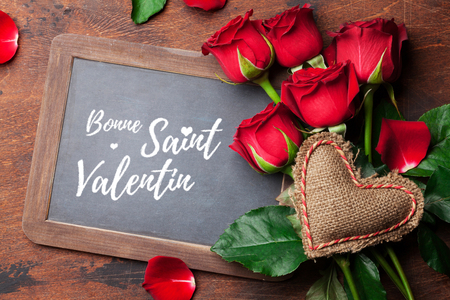 Valentine's day greeting card with red rose flowers bouquet on wooden background. Bonne Saint Valentin France. Top view with chalkboard for your greetings