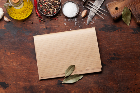 Set of various spices and herbs on wooden background. Top view with cookbook for your recipe. Flat lay