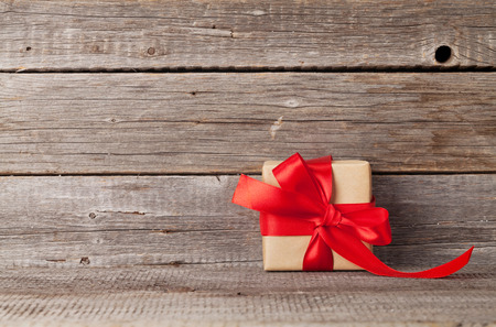 Valentines day or christmas greeting card with gift box in front of wooden wall. With space for your greetings Stock Photo