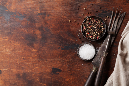 Spices for meat and kitchen utensils. Salt and pepper on wooden cooking table. Top view with space for your text Stock Photo