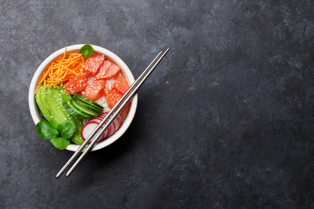 Poke bowl with salmon and vegetables. Traditional Hawaiian raw fish salad. Top view with copy space Stock Photo