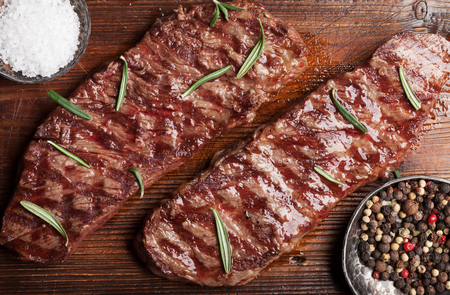 Top blade or denver grilled steak over cutting board. Top view