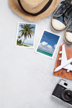 Travel vacation background concept with sun hat, camera, passport, airplane toy and weekend photos on stone backdrop. Stok Fotoğraf
