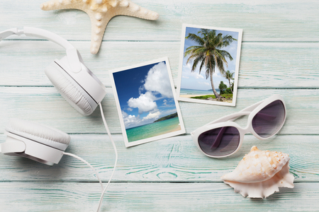 Travel vacation background concept with sunglasses, headphones and weekend photos on wooden backdrop. Top view. Stockfoto