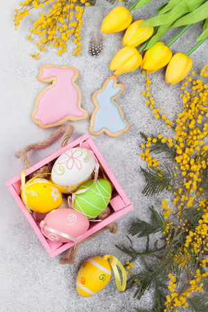 Easter eggs and yellow flowers. Greeting card. Top view