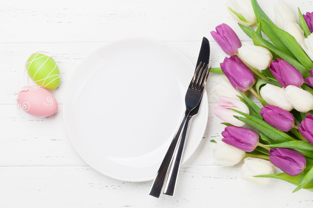 Easter greeting card with tulip flowers bouquet and easter eggs. Top view over white wooden table with space for your greetings