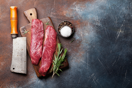 Raw top blade or denver steak cooking on cutting board cooking. Top view with copy space