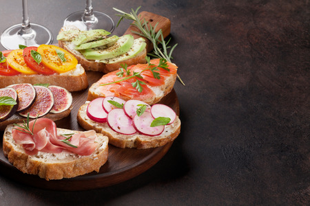 Brushetta or traditional spanish tapas. Appetizers italian antipasti snacks set on wooden board with rose and white wine. With space for your text