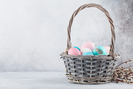 Easter greeting card with pussy willow and colorful easter eggs in basket in front of stone wall. With space for your greetings